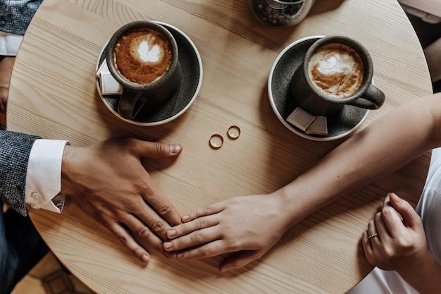 Мужчина и женщина пара молодоженов держатся за руки кольцами в кафе с чашкой кофе