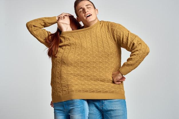 男性と女性のカップルが1つのセーター、恋人の強いカップルでポーズ