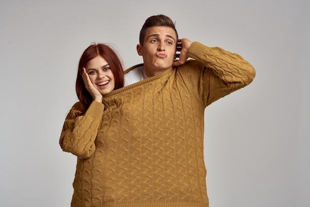 Мужчина и женщина пара позирует в одном свитере влюбленных