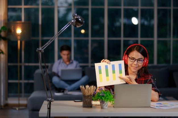 남자와 여자 커플은 해질녘에 거실에 앉아 노트북 컴퓨터 작업을 하고 있으며, 여성은 노트북을 통해 팀이나 고객에게 그래프와 차트를 제시합니다. 집 개념에서 작동합니다.