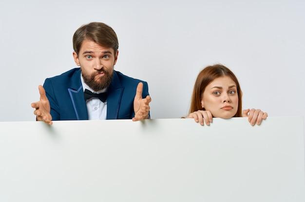 男性と女性は、白いバナー広告のプレゼンテーション担当者をトリミングしました。