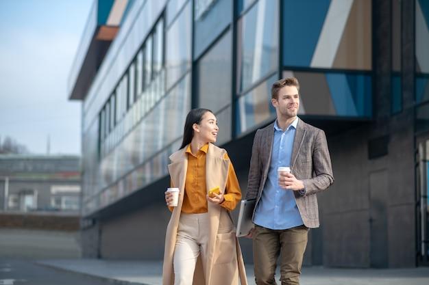 話しながら横断歩道で通りを横断する男女
