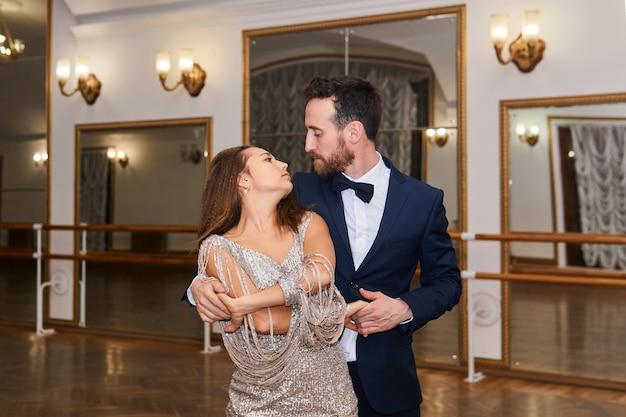 남자와 여자는 춤을 추고 거울이 있는 빈티지 홀에서 서로를 봅니다.