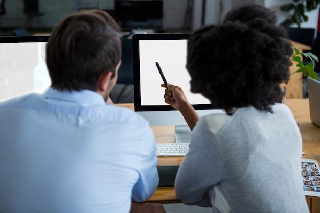 デスクトップpcを介して議論する男女