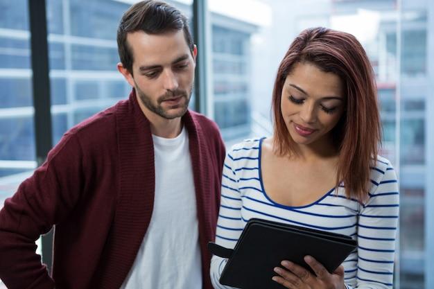 デジタルタブレット上で議論する男と女