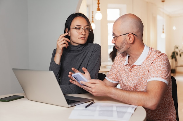 ノートパソコンを持ってカフェに座って仕事の問題を話し合う男女