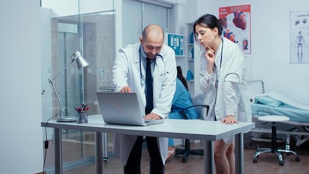 남자와 여자 의사는 환자와 의사가 복도를 걷고 있는 현대적인 분주한 개인 병원에서 환자 치료에 대해 이야기하고 있습니다. 백그라운드에서 일하는 간호사. 의료 시스템 실무자