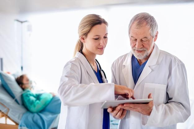 病院でタブレットを話している男性と女性の医師、コロナウイルスの概念。