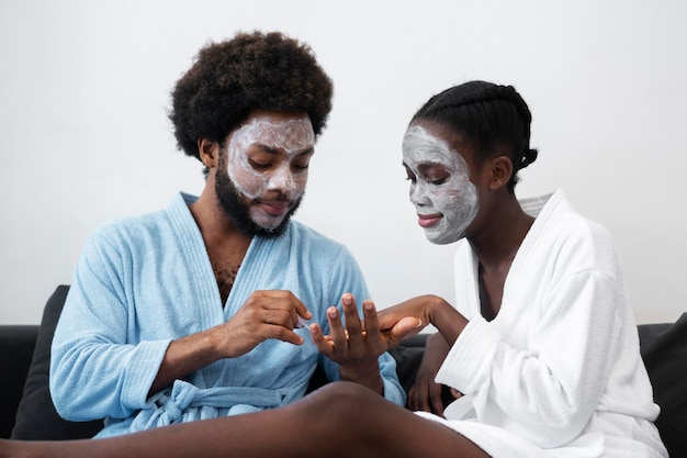 自宅で美容トリートメントをしている男女