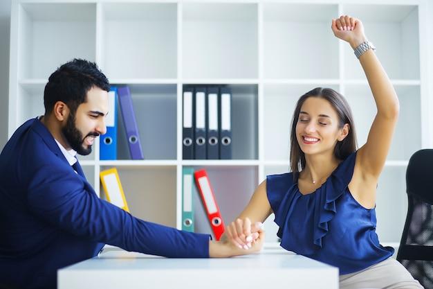 Мужчина и женщина делают армрестлинг в офисе