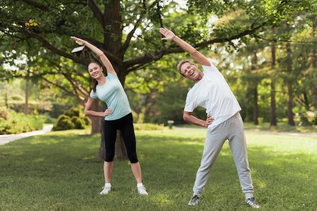 男と女が公園で練習をしています。彼らはウォームアップします。