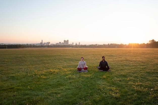 Мужчина и женщина вместе занимаются йогой на открытом воздухе
