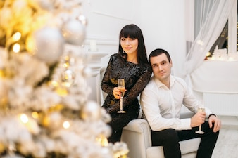 Man and woman dressed for a festive dinner stand before a shiny Christmas tree