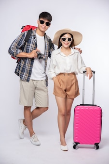 Мужчина и женщина, одетые в очки, путешествуют с чемоданами