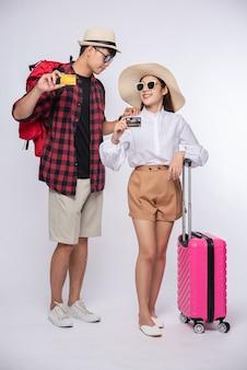 남자와 여자는 여행 가방을 들고 안경을 차려 입다.