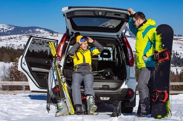 Suv車の近くのスキー用具に身を包む男女。背景の山