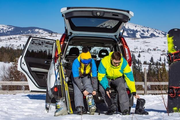 Мужчина и женщина одеваются в лыжное снаряжение возле внедорожника. горы на фоне
