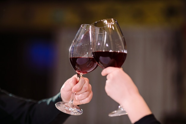 레드 와인을 마시는 남자와 여자. 사진에서 안경으로 손을 클로즈업하십시오.