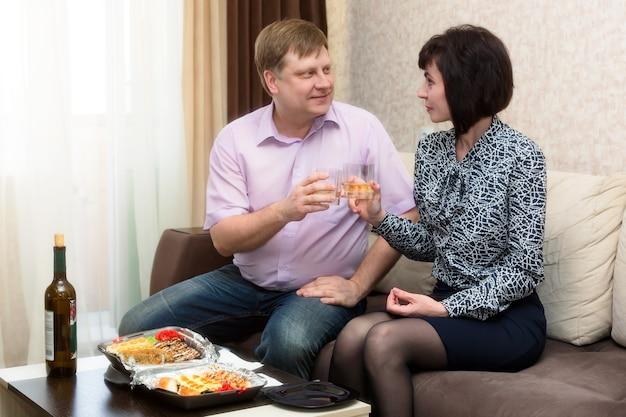 Мужчина и женщина пьют вино на диване, первое свидание