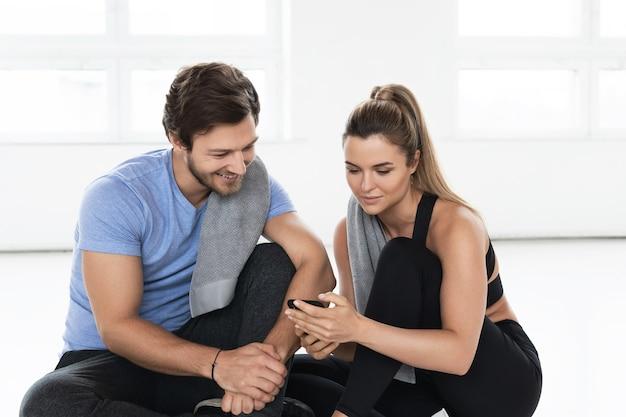 Мужчина и женщина во время тренировки в тренажерном зале. девушка показывает своему товарищу по команде новое фитнес-приложение.