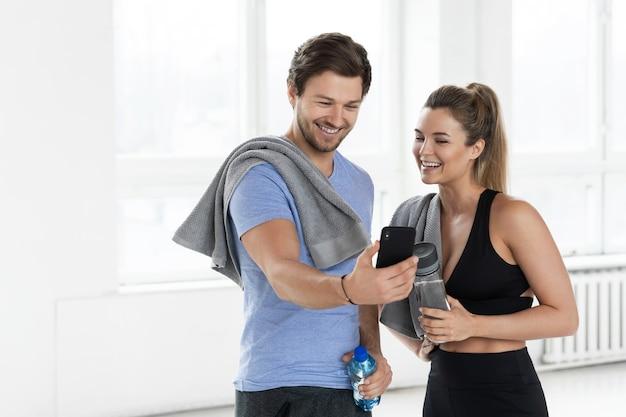 Мужчина и женщина во время тренировки в тренажерном зале. парень показывает товарищу по команде новое фитнес-приложение на смартфоне.