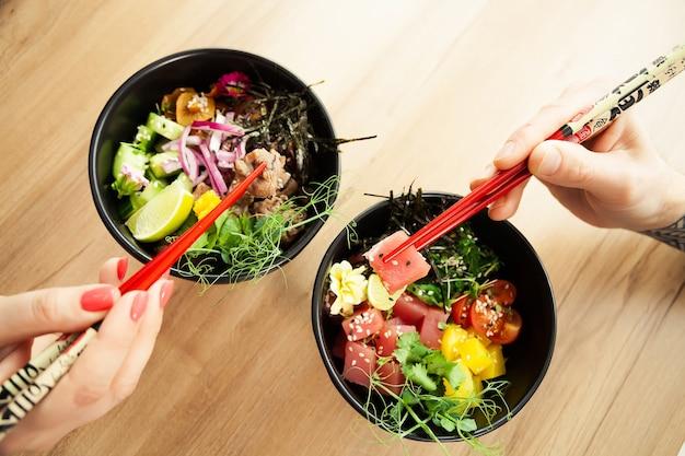 젓가락으로 찌르는 샐러드를 먹는 남자와 여자. 그릇에 참치 샐러드를 담그십시오. 식당에 있는 사람들은 젓가락으로 샐러드를 먹습니다. 아시아 해산물 샐러드 개념입니다.