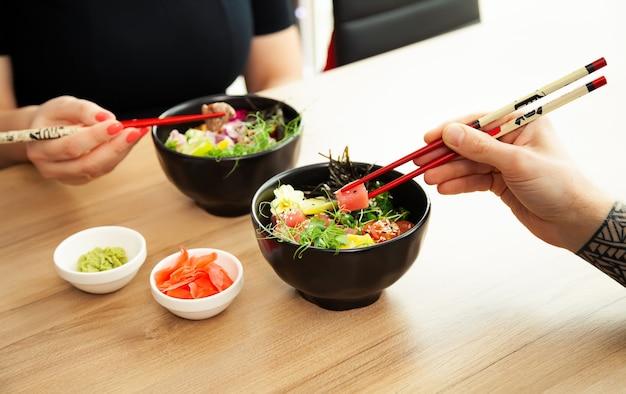 레스토랑에 있는 그릇에 젓가락으로 참치 샐러드를 얹은 포케 샐러드를 먹는 남녀