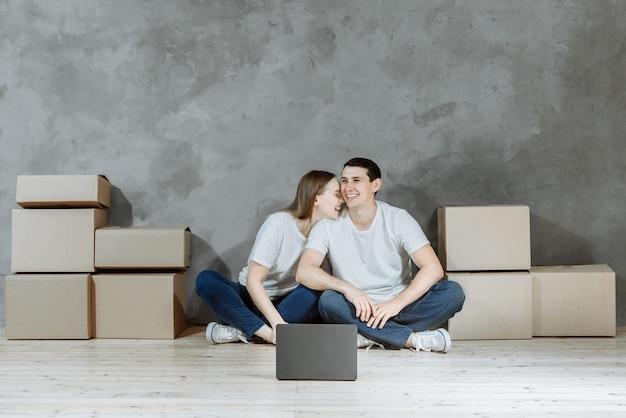 노트북 노트북 및 새 아파트에 상자와 남자와 여자 가족.