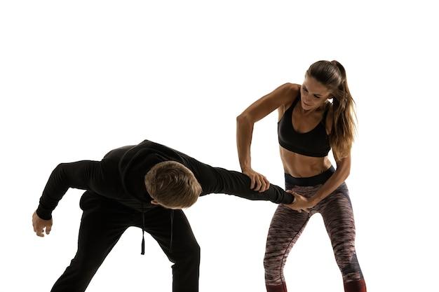 Мужчина и женщина борются на белом, концепция самообороны женщин