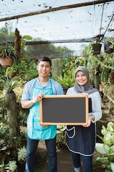 空白のブラックボードを保持している男と女の庭師 Premium写真