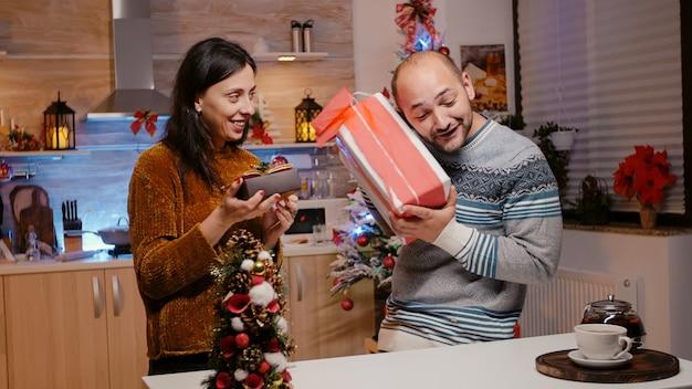 크리스마스에 서로에게 선물 상자를 주는 남자와 여자