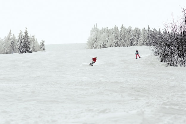 Мужчина и женщина спускаются с холма на сноубордах