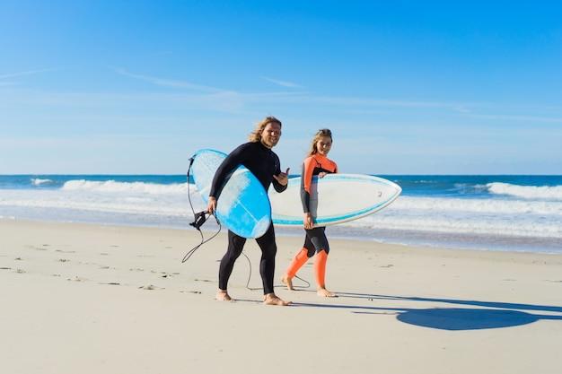 男と女はサーフボードで海に行きます。男と女の子はサーフィンに行く