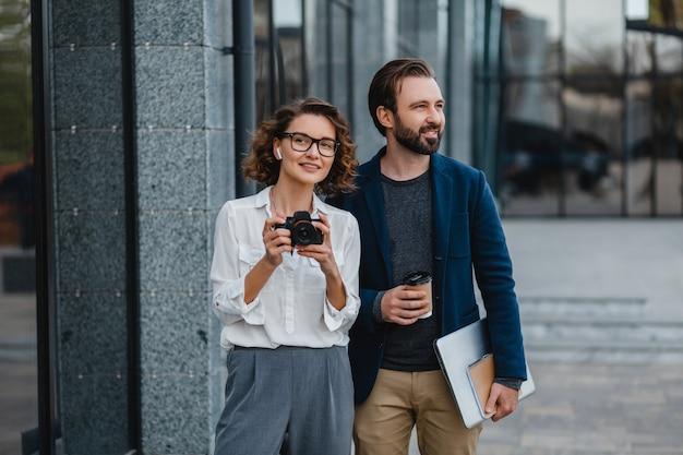 Мужчина и женщина идут по лестнице в центре города, держат кофе и ноутбук, обсуждают