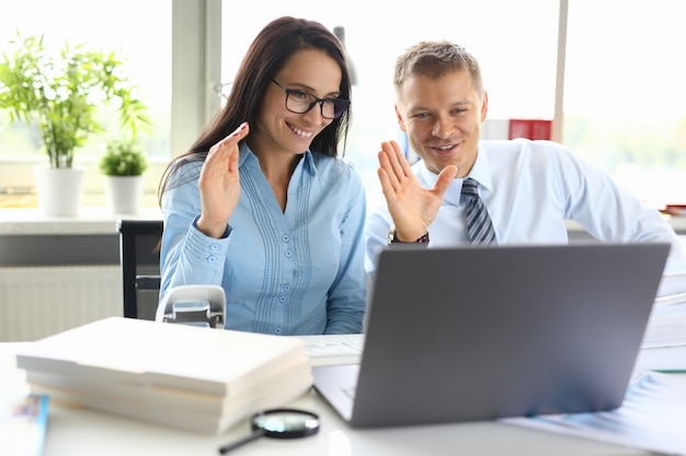 Мужчина и женщина приветствуют собеседника рукой на онлайн-звонке на ноутбуке
