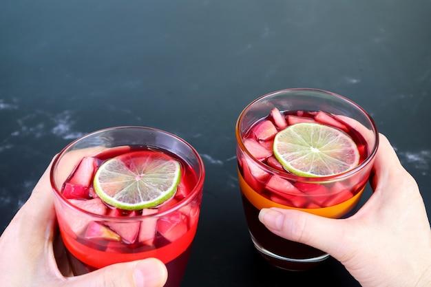 自家製サングリアのグラスを持っている男性と女性の手 Premium写真