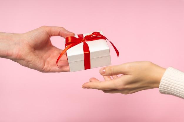 남자와여자가 손을 분홍색 배경에 발렌타인 선물을 들고
