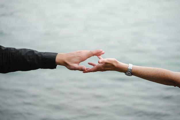 男性と女性の手が水の近くで手を差し伸べる