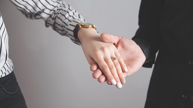 Мужчина и женщина руки с обручальным кольцом.