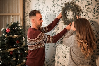 Man and woman hanging Christmas wreath near decorated fir tree