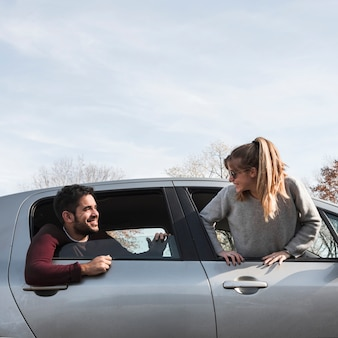 Man and woman hanging out of car window