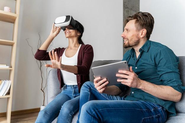 Мужчина и женщина веселятся дома, играя с гарнитурой и планшетом виртуальной реальности