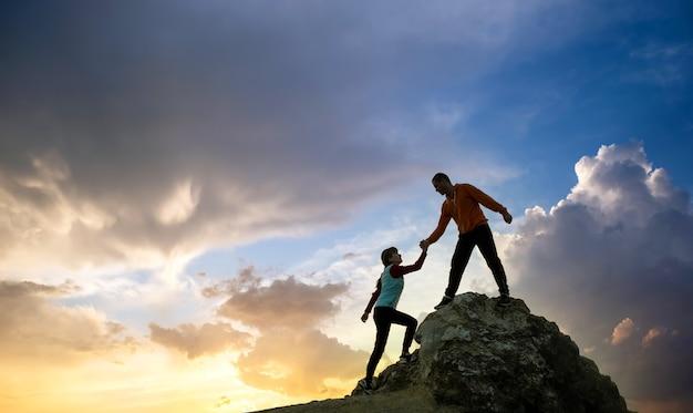 山の日没時に大きな石を登るために互いに助け合う男性と女性のハイカー。夕方の自然の中で高い岩に登るカップル。観光、旅行、健康的なライフスタイルのコンセプト。