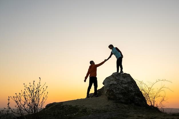 山の日没時に大きな石を登るために互いに助け合う男性と女性のハイカー。