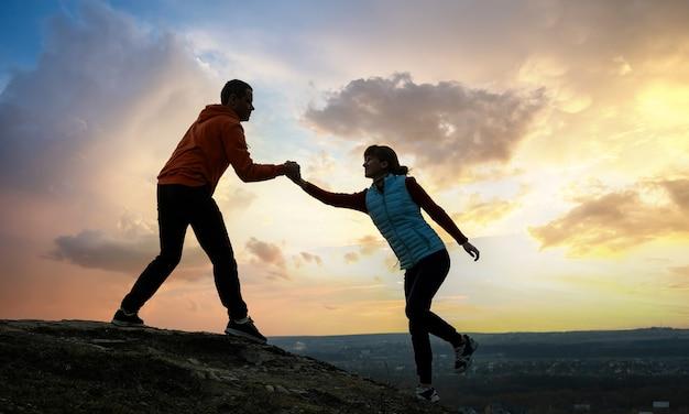 山の日没時に石を登るために互いに助け合う男性と女性のハイカー。