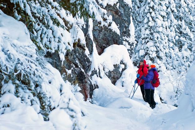 겨울 눈 덮인 산 숲에서 남자와 여자 등산객