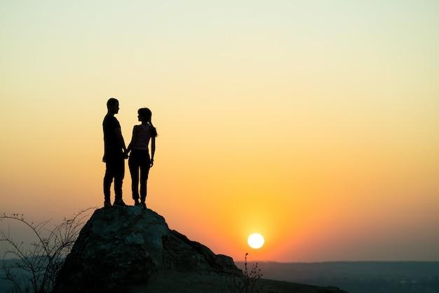 山の夕暮れ時に大きな石の上に立っている男性と女性のハイカー。夜の自然の高い岩の上に一緒にカップル。観光、旅行、健康的なライフスタイルのコンセプト。