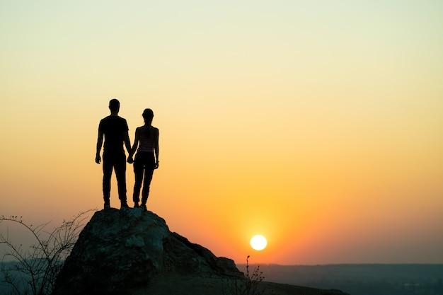 山の夕暮れ時に大きな石の上に立っている男性と女性のハイカー。