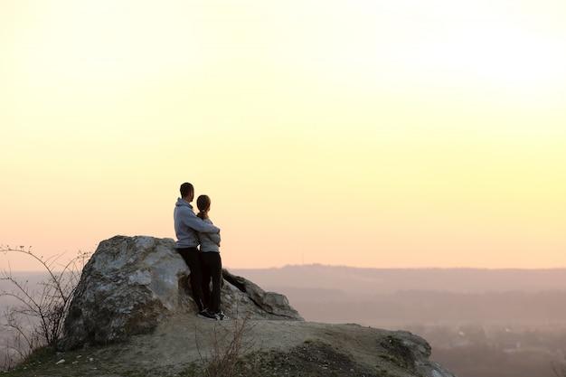 山の夕暮れ時に大きな石の上に立っている男性と女性のハイカー。夜の自然の中で高い岩をカップルします。観光、旅行、健康的なライフスタイルのコンセプト。