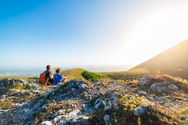 イタリア、アペニン山脈、モンテクッコのウンブリア地方の山々でハイキングをする男女。山の頂上で一緒に夕日を見ているカップル。夏の野外活動。
